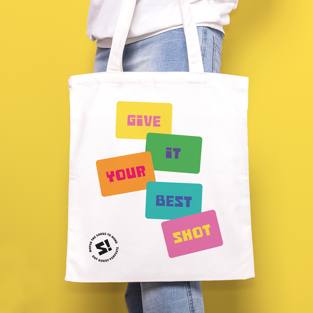 Tote bag for Schnap! Game, showing a bright card deck reading the words 'Give It Your Best Shot'